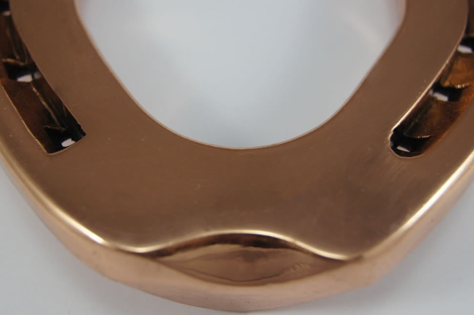 Close up shot of a polished copper horse shoe created by Ben Chamberlain